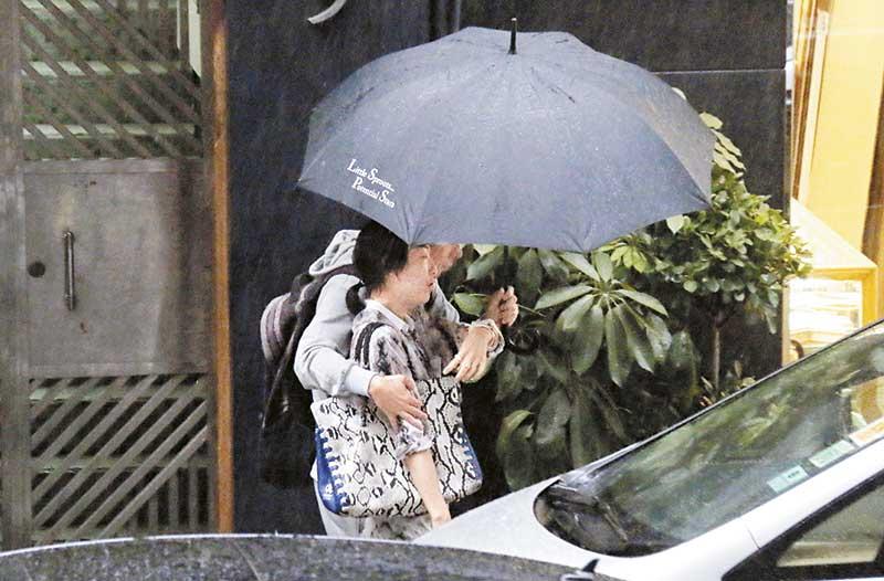 小俩口买完巧克力离开,出门口时突然下大雨,安仔一手拿伞一手将老婆拥入怀,Sammi如小鸟依人般依偎在老公怀中。