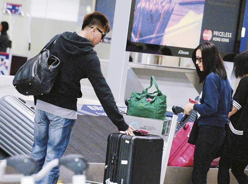 帮忙取行李 两人到达行李输送带前,马国明负责提取属于两人的4箱行李,唐咏诗则守着手推车兼看守两人随身物品,尽显默契。